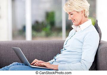 elderly woman using laptop computer - happy elderly woman...