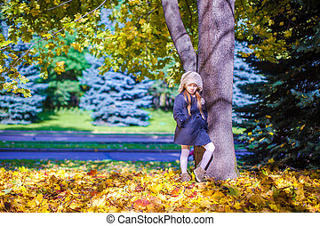 Little beautiful girl on the autumn meadow near big maplr in a sunny fall day