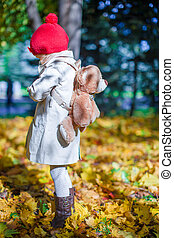 Little cute girl with a backpack-bear walks in the autumn...