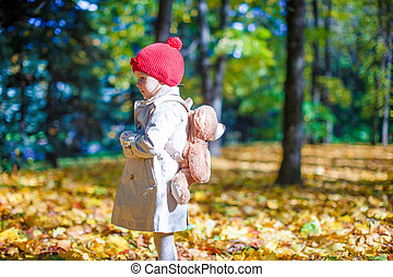 Little girl with a backpack-bear walks in the autumn forest...