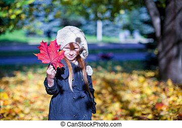 Close-up red maple leaf in the hands of little girl on beautiful fall day
