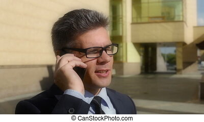 Business call - Tilt down of a mature businessman calling...