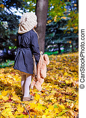 Rear view of charming little girl with a backpack-bear in...