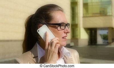 Elegant communication - Elegant business lady talking on the...