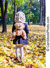 Rear view of charming little girl with a backpack-bear...