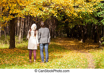 Back view of Young couple in love on the big autumn meadow...