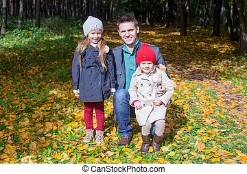 Young father and his two adorable little daughters walking in the autumn park enjoying a sunny day