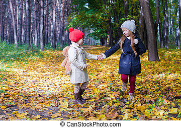 Two beautiful adorable girls walking in the fall forest at warm sunny autumn day