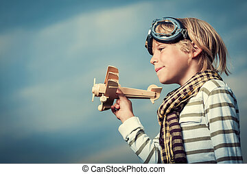 Happiness - Little boy with a plane on sky background