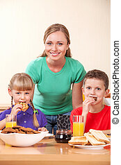 Young mother together with two children eat breakfast at kitchen