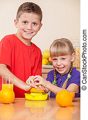 Kids are squeezing orange juice, helping their parents to...