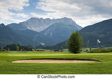 golf course with sand bunker and hole flag in mountain...