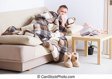 Sick man with tissue - Man laying on sofa uder natural...
