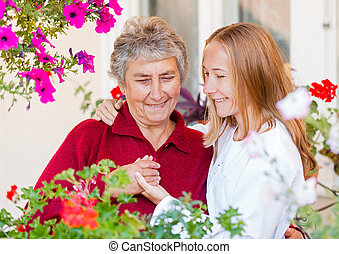 Elderly care - Happy elderly woman and her helpful assistant