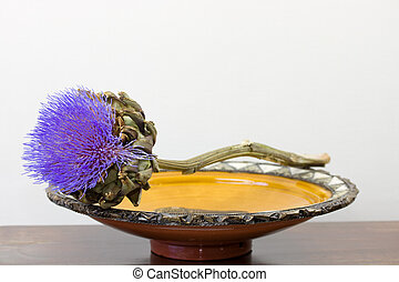 purple artichoke flower on Moroccan dish isolated on white