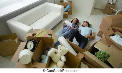 Couple belongings - Positive young people lying among...