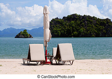 Exotic Vacation - Sunbeds and parasol on a tropical sandy...