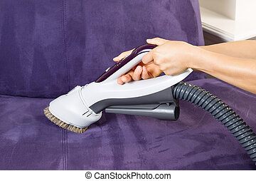 Cleaning Leather Sofa with Vacuum Brush - Horizontal photo...