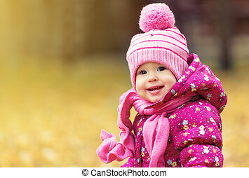 happy baby girl child outdoors in the park in autumn on walk