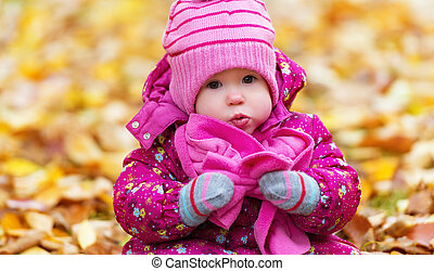 funny happy baby girl child outdoors in the park in autumn...