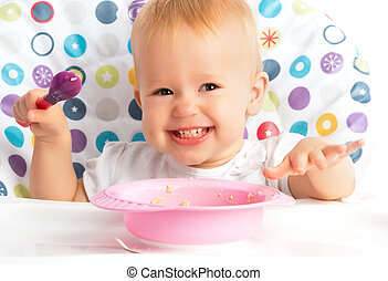 happy baby child eats itself with a spoon - cheerful happy...