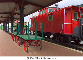 Caboose parked in front of train station platform