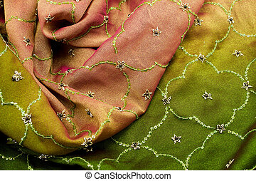 Pink and green satin textile background (close up)