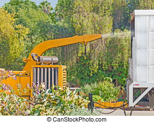 Industrial yellow wood chipper machine and truck profile -...