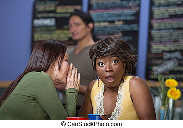 Lady Whispering to Friend - Woman whispering to another in...