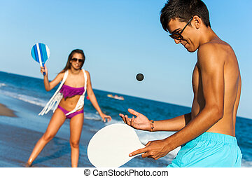 teen couple playing smash ball beach tennis - Teen couple in...