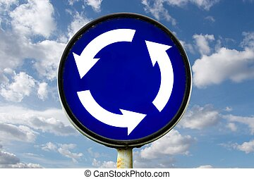 Roundabout traffic sign against blue sky
