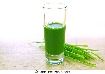 Wheatgrass in glass - Wheathgrass juice on wood background