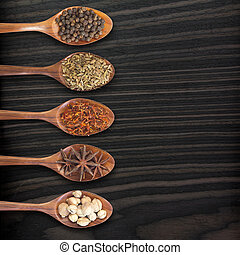 Set of 5 spices on a wooden spoon, on wood background