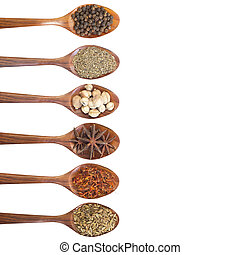 Collection of 6 spices on a wooden spoon. isolated on a...