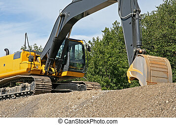 Excavator with bucket shovel - Yellow excavator on top of...