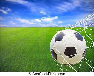 Soccer ball in gold net - soccer ball in goal net over blue...