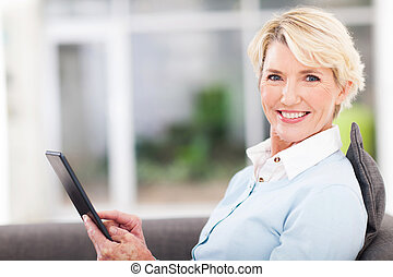 elegant middle aged woman using tablet pc