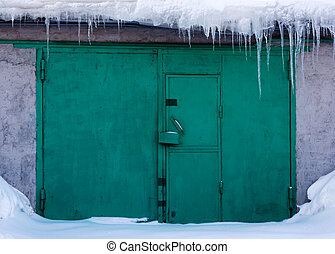 Green gates in snow, icicles droop, lock, doorknob