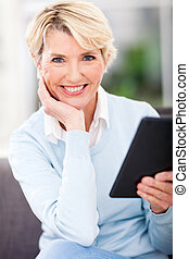 middle aged woman holding tablet pc - happy middle aged...