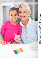 little girl with her grandmother drawing at home