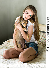 Young woman with little dog sitting on bed