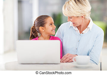 little girl and grandma using laptop - cheerful little girl...