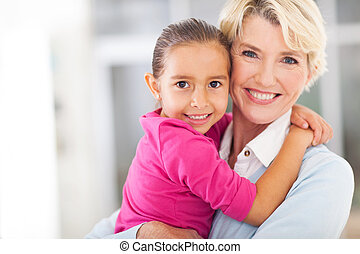 happy grandmother with granddaughter embracing at home