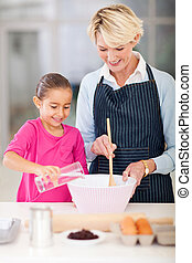 grandmother and granddaughter baking cookies - happy...