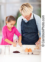 granddaughter and grandmother baking cookies together in...