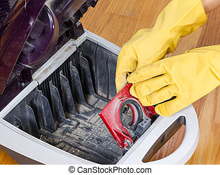 Completing Cleanup of Vacuum Cleaner - Photo of gloved hands...