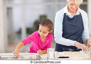 grandmother baking cookies with granddaughter - senior...
