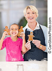 happy little girl and grandmother holding just baked...