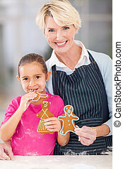 little girl eating gingerbread cookie grandma just baked -...