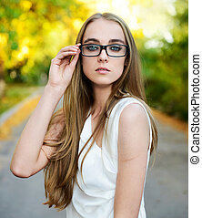 Portrait of young attractive blonde woman wearing eyeglasses...